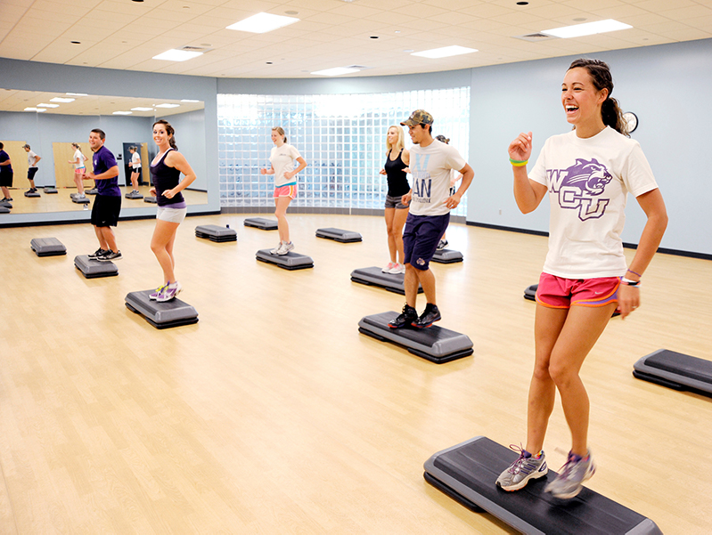 students perform an exercise routine together in an exercise class