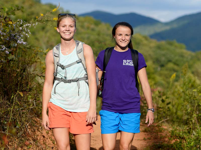 two female students walk on a hiking trail