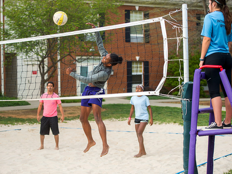 students play volleyball in a sand court outside