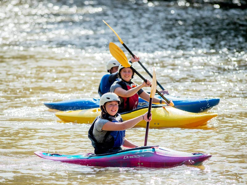 students smile while paddling kayaks in gentle water